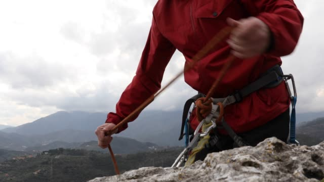 rock climber organizes gear on cliff summit - protezione video stock e b–roll
