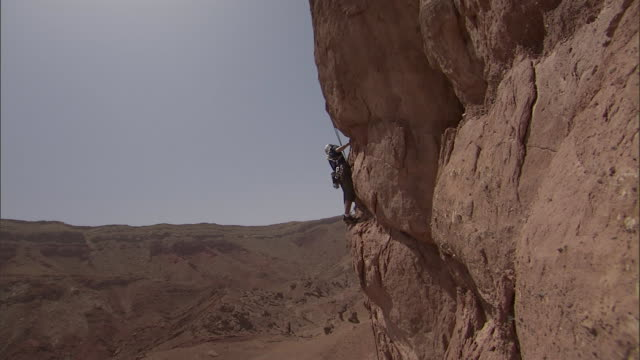 a rock climber perches on a small cliff ledge. - challenge stock videos & royalty-free footage
