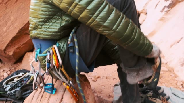 rock climber preparing for a climb - safety harness stock videos & royalty-free footage