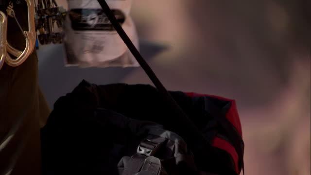 vidéos et rushes de a rock climber pulls a chalk bag out of his backpack. - harnais de sécurité