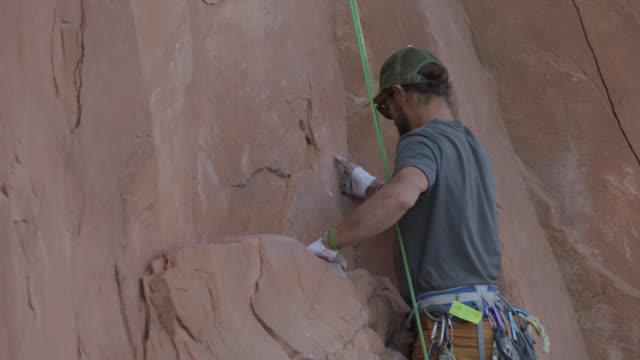 vidéos et rushes de slo mo. rock climber pulls himself up to new handholds as he ascends steep rock face. - lutte concepts