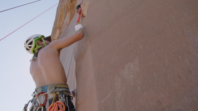 stockvideo's en b-roll-footage met rock climber pulls himself up with rough handholds as he ascends steep rock face. - touw