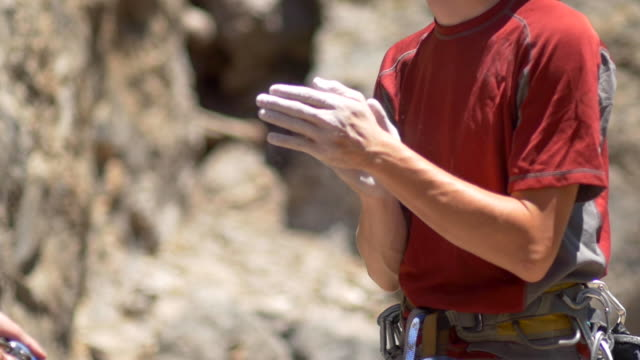 a rock climber putting chalk on his hands for better grip. - slow motion - sicurezza sul posto di lavoro video stock e b–roll