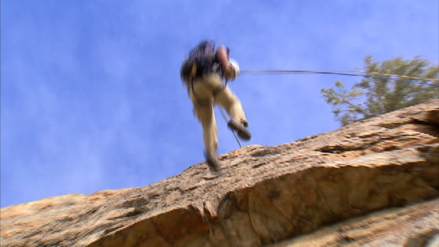 ws la zo rock climber repelling down cliff face / provo, utah, usa - abseiling stock videos & royalty-free footage