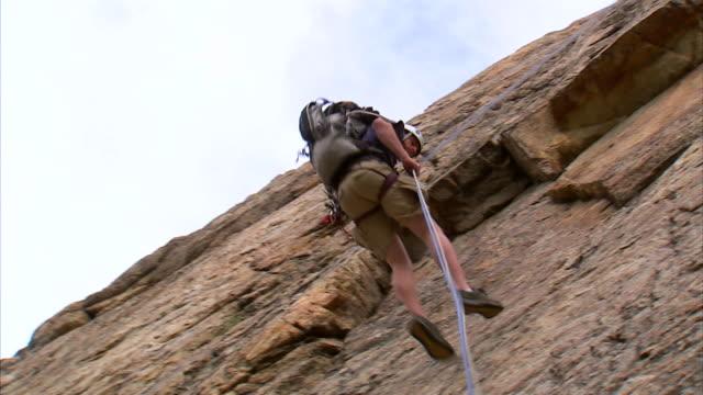 WS LA TD Rock climber repelling down cliff face / Provo, Utah, USA