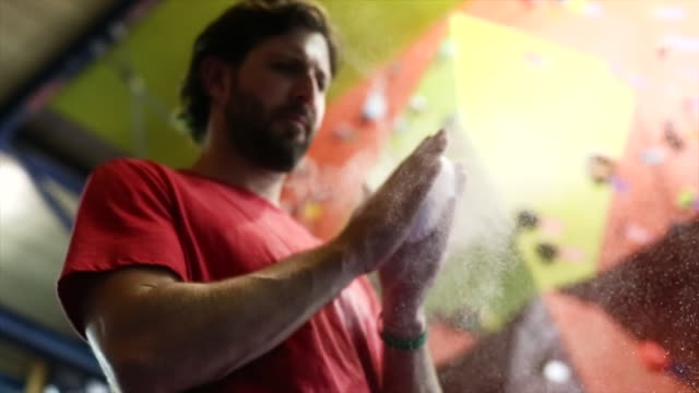 rock climber rubbing chalk on his hands - kletterwand kletterausrüstung stock-videos und b-roll-filmmaterial