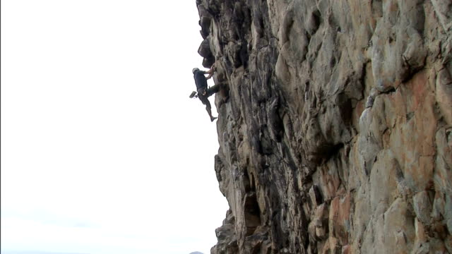 a rock climber scales a rock face. - rock face stock videos & royalty-free footage