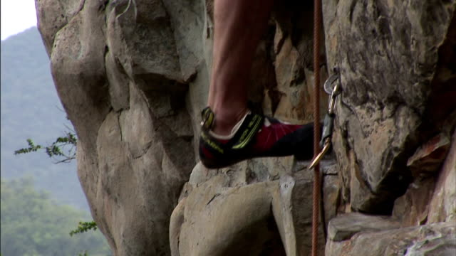 a rock climber scales a rock face with the help of a rope. - felswand stock-videos und b-roll-filmmaterial