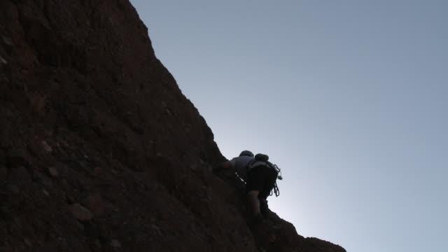 rock climber scaling cliff - 中年の男性だけ点の映像素材/bロール