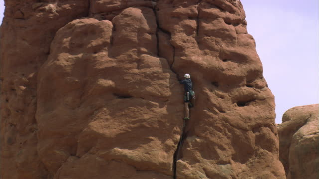 zo rock climber scaling up large rock formation at arches national park / utah, united states - zoom out stock videos & royalty-free footage
