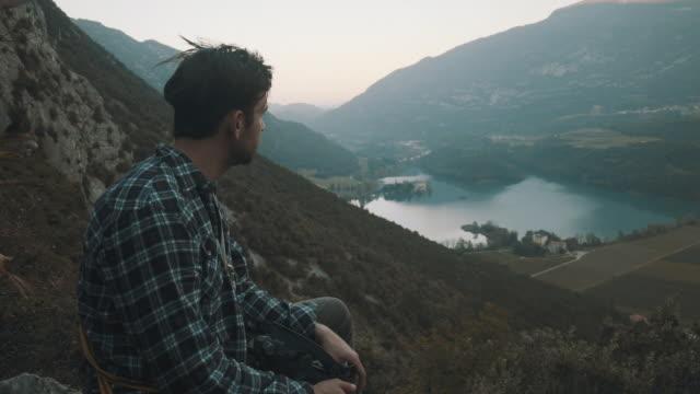 vidéos et rushes de rock climber sit on top of cliff in italy - rock face