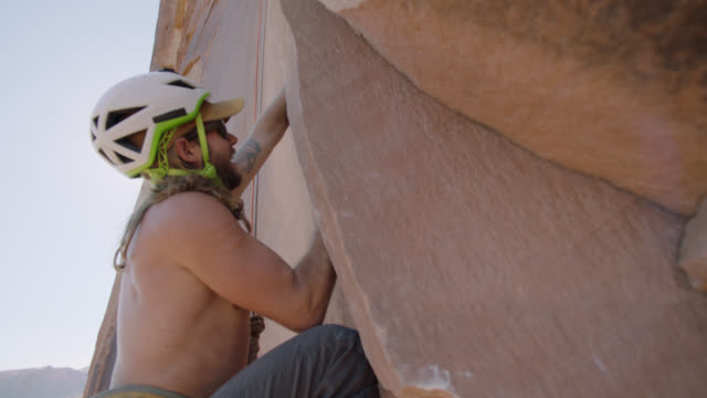 rock climber smiles as he pulls himself up with strong handholds as he ascends steep sandstone rock face. - hoisting stock videos & royalty-free footage
