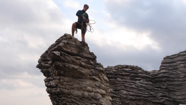 rock climber stands on summit of sea stack pinnacle, coils rope - surf rock stock videos & royalty-free footage