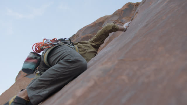 slo mo. rock climber stretches flat against rock face as he reaches for the next handhold on moab climbing expedition. - hoisting stock videos & royalty-free footage