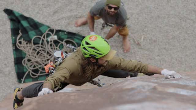 SLO MO. Rock climber stretches for hand and footholds on steep rock face as belayer looks up from below.