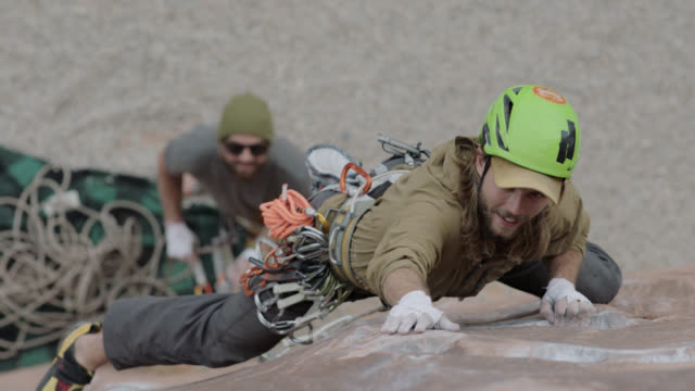 slo mo. rock climber stretches to grip and secure hand and footholds on steep rock face as belayer looks up from below. - safety harness stock videos & royalty-free footage