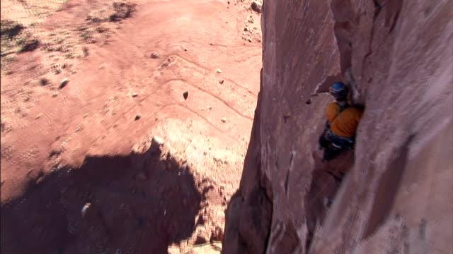 a rock climber tosses something while balancing on a canyon wall. - ロッククライミング点の映像素材/bロール