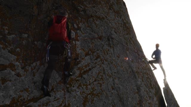 vídeos de stock, filmes e b-roll de alpinista atravessa a parede de rocha ao companheiro de equipa, floco vertical - corda de escalada