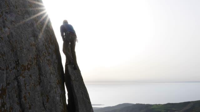 Rock climber traverses rock wall to vertical flake