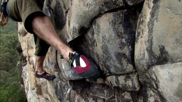 a rock climber tries to find a footing on a rock face. - rock face stock videos & royalty-free footage