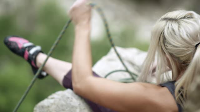 vídeos de stock, filmes e b-roll de rock climber woman pulling rope to top of route. - corda de escalada