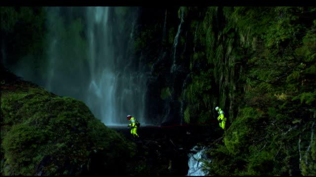 vídeos de stock e filmes b-roll de rock climbers ford a river near a powerful waterfall. - queda de água