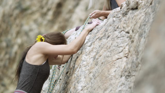 Rock climbing woman, helped to the top by her friends.