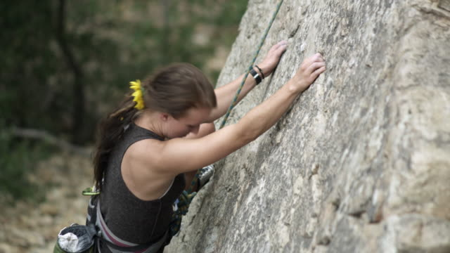 vídeos de stock, filmes e b-roll de rock climbing woman, with dreads, finding holds. - corda de escalada