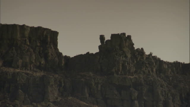 Rock columns rise above a cliff. Available in HD.
