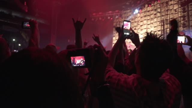 vídeos de stock e filmes b-roll de 4k montage - rock concert stadium show crowd mobile phone filming - música heavy metal