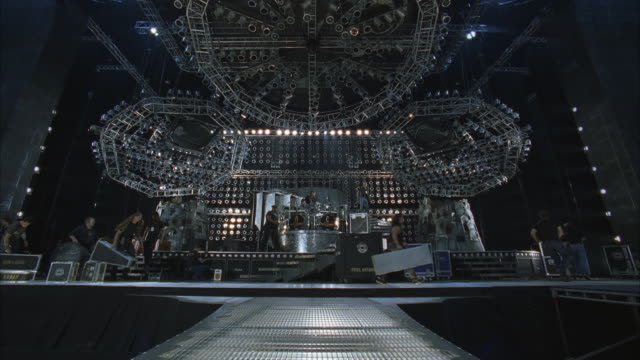 ws rock concert stage, workmen setting up stage, moving speakers and instruments - リハーサル点の映像素材/bロール