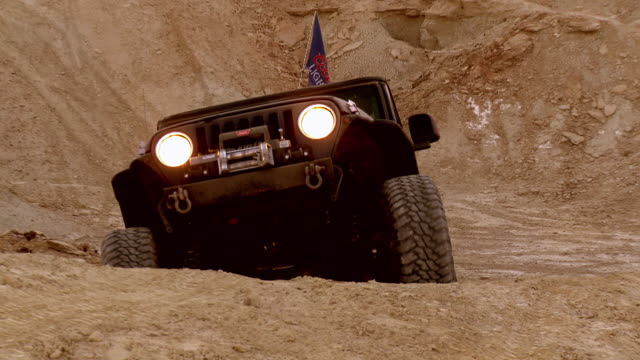 ms zo rock crawling jeep with headlights on at dusk climbing up steep incline / salton city, california, usa  - 4x4 stock videos and b-roll footage