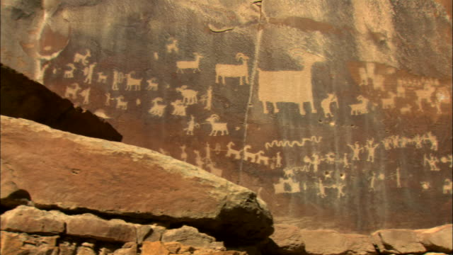 ms, pan, rock face covered with petroglyphs representing hunting scenes, utah, usa - human representation stock videos and b-roll footage