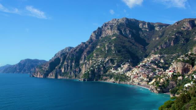 rock face surrounds positano town, amalfi coast, italy - mar mediterraneo video stock e b–roll