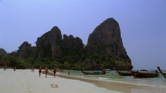 ms, rock formation and long tail boats moored at  rai lay beach, krabi, thailand - fan palm tree stock videos & royalty-free footage