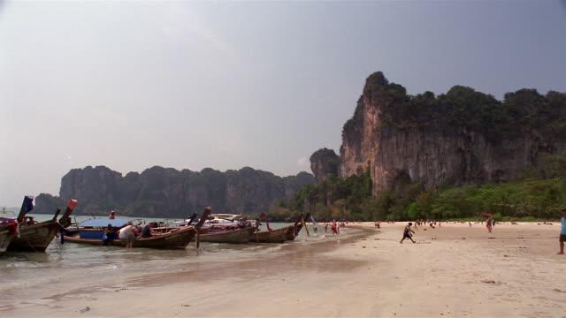 ws, rock formation and long tail boats moored at  rai lay beach, krabi, thailand - solfjäderspalm bildbanksvideor och videomaterial från bakom kulisserna