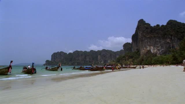 vídeos y material grabado en eventos de stock de ws, rock formation and long tail boats moored at  rai lay beach, krabi, thailand - palmera abanico