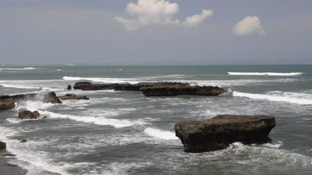 ws rock formation and surf at echo beach, surfing beach, batubelig, asia audio / seminyak, bali, indonesia - surf rock stock videos & royalty-free footage