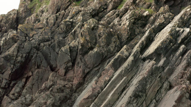 rock formations at the base of a cliff in scotland - rock strata stock videos & royalty-free footage
