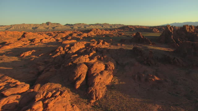 ws aerial rock formations of different red colors in valley of fire in morning with sunlight / nevada, united states - 幻想点の映像素材/bロール