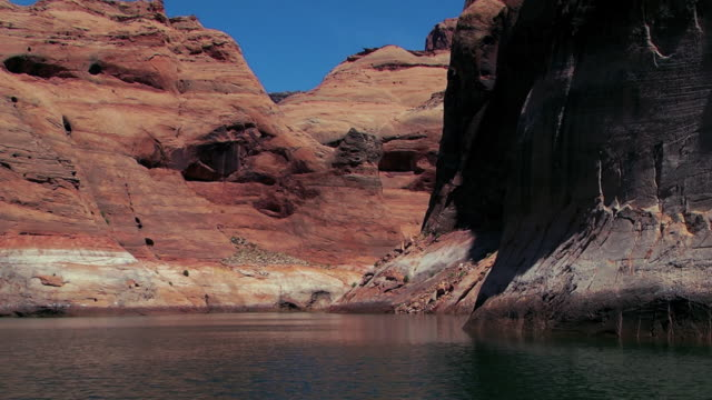 stockvideo's en b-roll-footage met rock formations on a cliff face tower over lake powell. - powellmeer