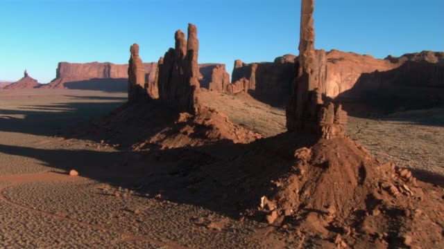 rock formations rise from the desert floor in monument valley. - butte rocky outcrop stock videos and b-roll footage
