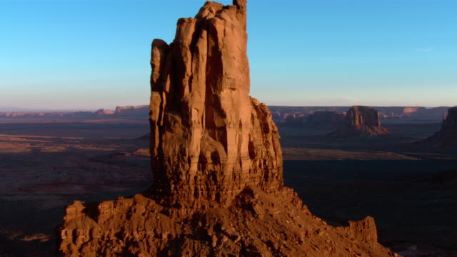 Rock formations rise from the desert floor in Monument Valley.