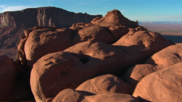 rock formations tower above the dessert in monument valley. - butte rocky outcrop stock videos and b-roll footage