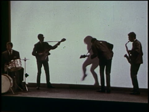 1964 rock group les dangers performing / silhouette woman dancing behind screen in background / music video - rocking stock videos & royalty-free footage