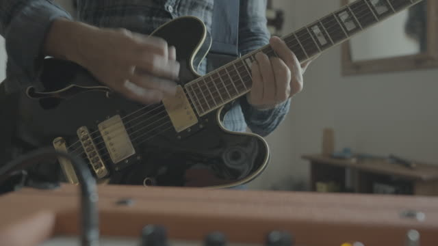 vidéos et rushes de guitariste de roche jouant la guitare à la maison - amplificateur