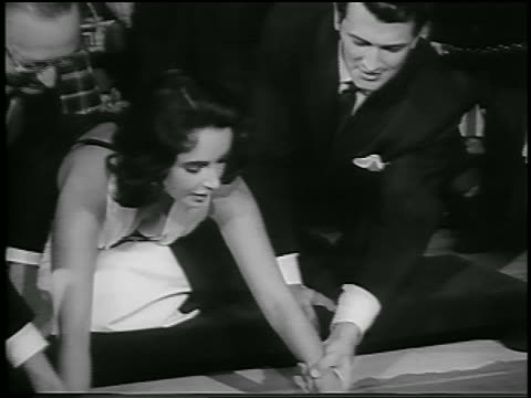 Rock Hudson helps Elizabeth Taylor put handprints in sidewalk at Grauman's / Hollywood