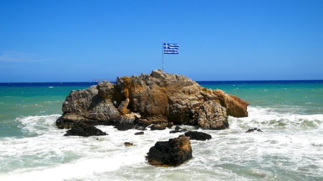 波と水の中の岩、そして上にギリシャの旗 - ギリシャ国旗点の映像素材/bロール