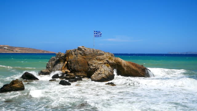 rock in water with waves, and a greek flag on top - greek flag stock videos & royalty-free footage