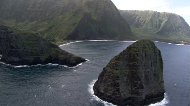 rock islands rise out of the pacific ocean along a mountainous coastline in hawaii. available in hd. - hawaii inselgruppe stock-videos und b-roll-filmmaterial